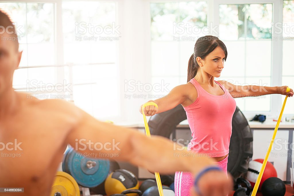 Image of two young sport enthusiasts, exercising in gym with rubbers....