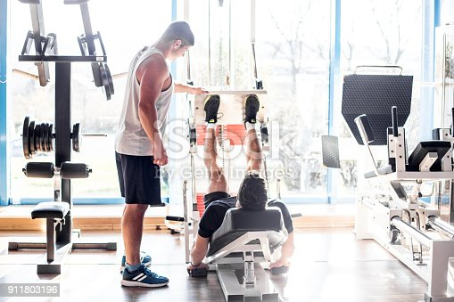 istock Fitness Instructor Assisting a Young Man at Weight Training 911803196