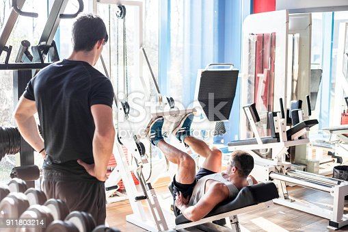 istock Fitness Instructor Assisting a Young Man at Weight Training 911803214