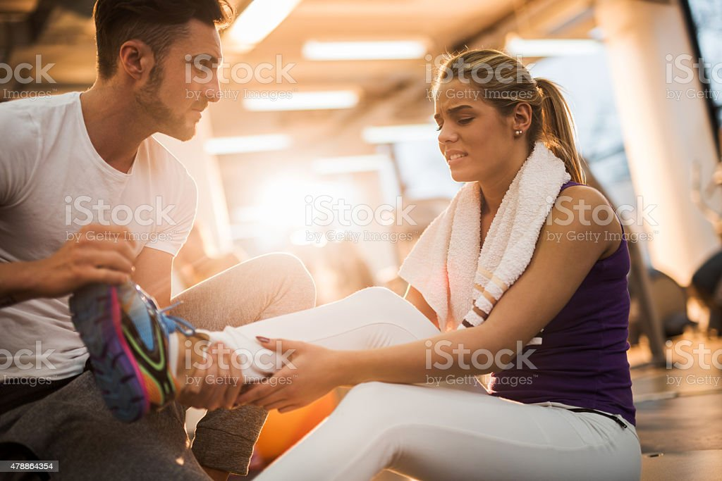 Fitness instructor assisting young woman who had injured herself. stock photo