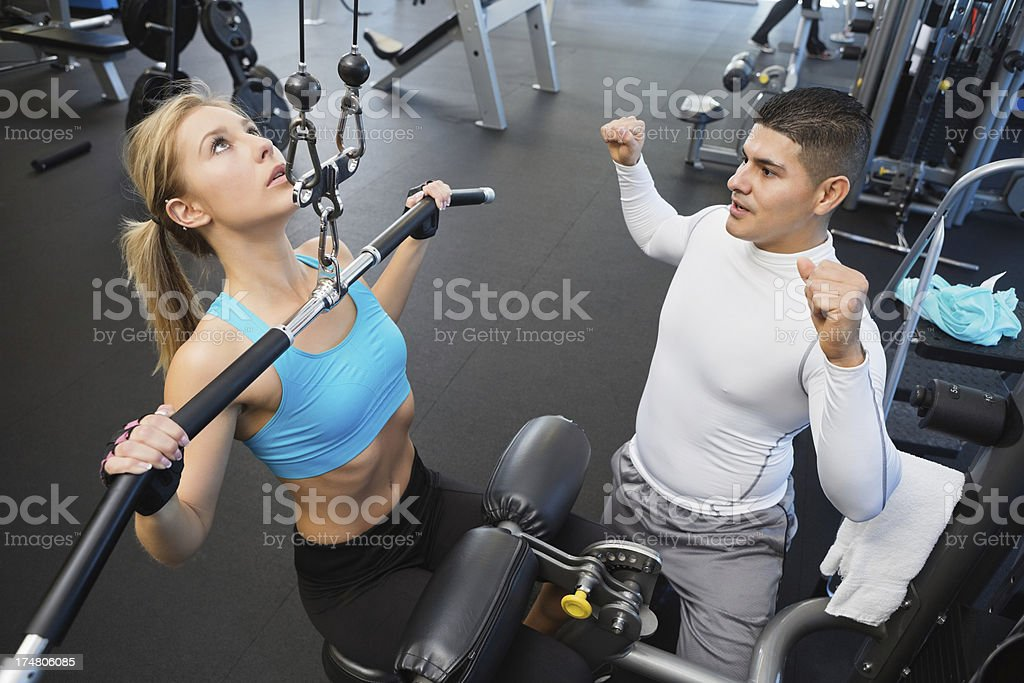 Fitness instructor demonstrating exercise weight lifting equipment in gym royalty-free stock photo