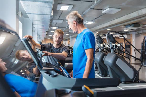 instrutor de fitness explicando plano de treinamento para idosos em academia - comodidades para lazer - fotografias e filmes do acervo