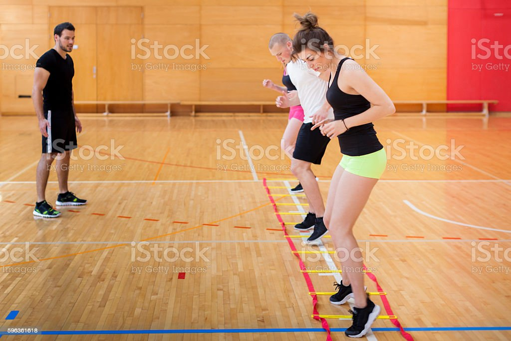 Fitness Instructor Following  Exercising of Young Athletes in Gym royalty-free stock photo
