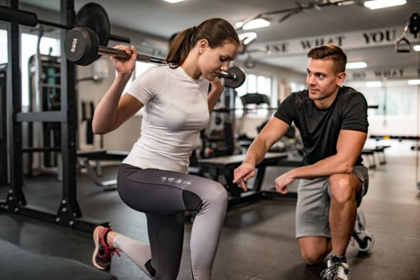 instructor de fitness guiando a la mujer joven cuando ella ejerce - entrenador personal fotografías e imágenes de stock
