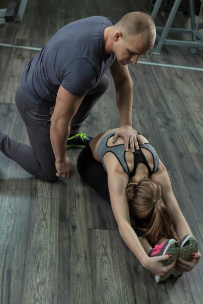 Ein Fitness-Trainer hilft einer Frau dehnen – Foto