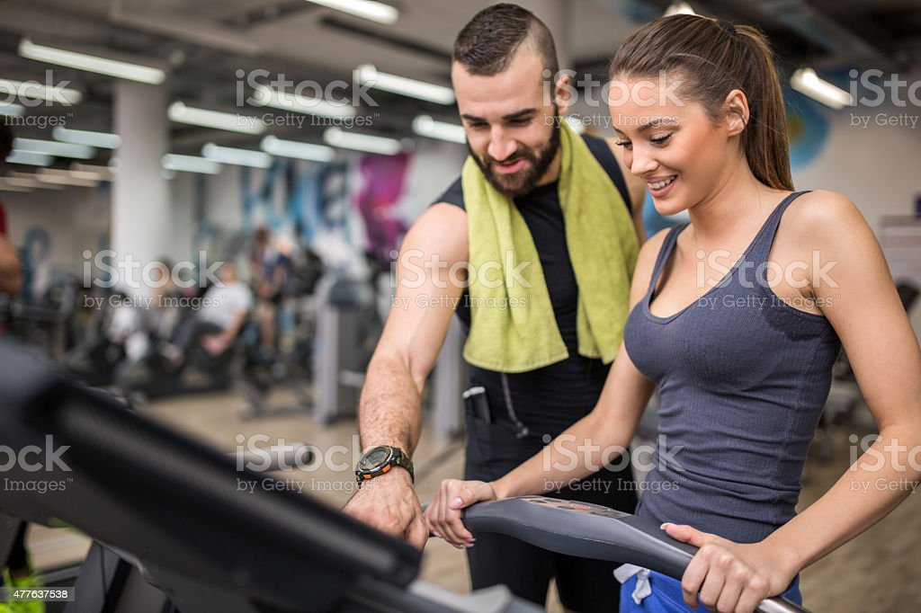 Fitness instructor helping a woman to adjust speed on treadmill. stock photo
