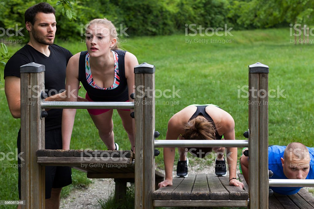 Fitness Instructor Helping Young Woman To Do the Exercise Correctly royalty-free stock photo