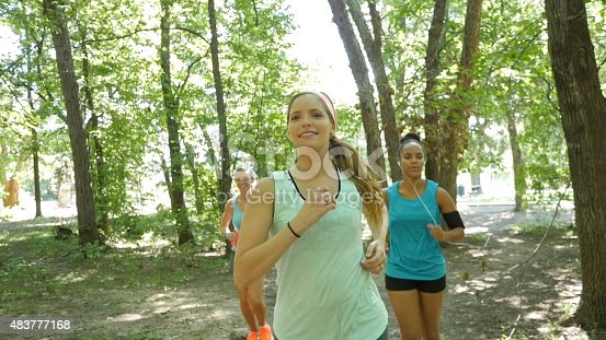 1051098428 istock photo Fitness instructor leading running club on dirt path in park 483777168