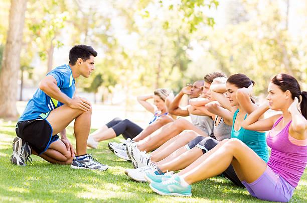 Fitness-Trainer motivieren dabei Sit-Ups im Park – Foto