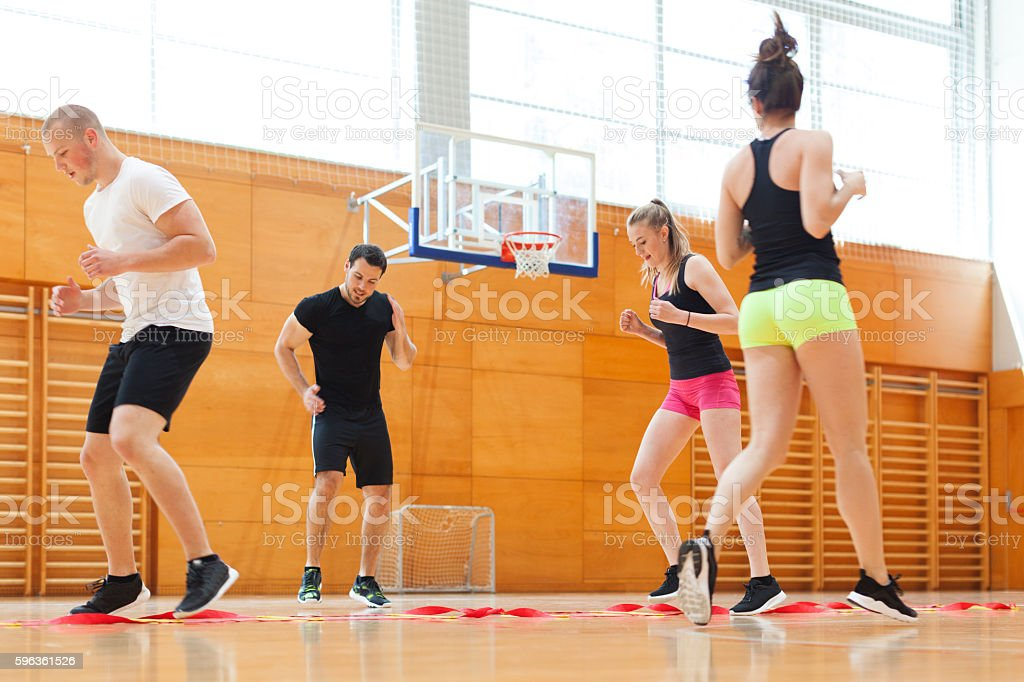 Fitness Instructor Motivating Young Athletes in Warm Up  Exercises royalty-free stock photo