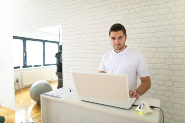 Fitness instructor using laptop at gym stock photo