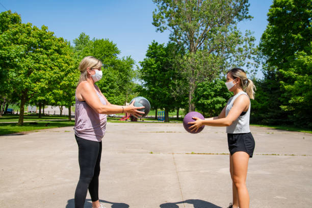 A fitness instructor working out with a mature female client outside in park. stock photo