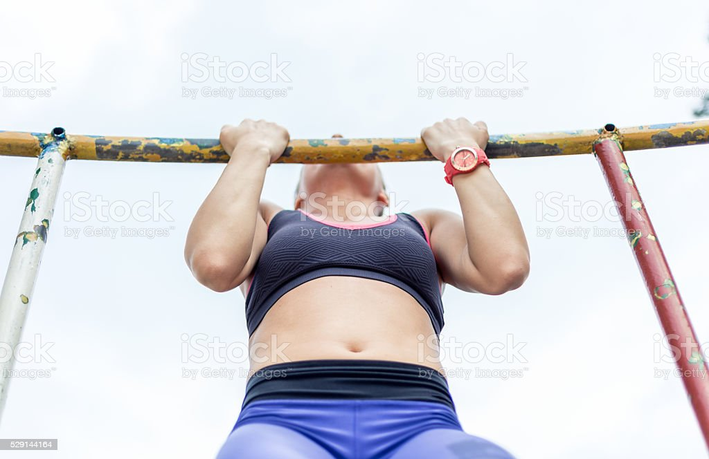fitness instruktor doing pull up in local park stock photo