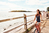 Cropped shot of a beautiful young woman riding her bicycle on the promenade