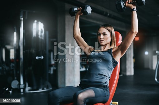 Shot of a young woman working out with weights in a gym