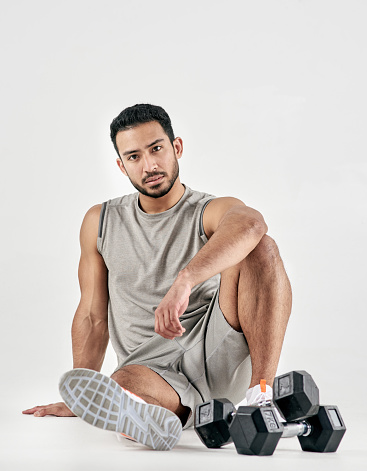 Studio portrait of a muscular young man posing with dumbbells against a white background