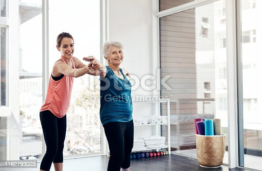 Shot of a fitness instructor helping a senior woman during a yoga class