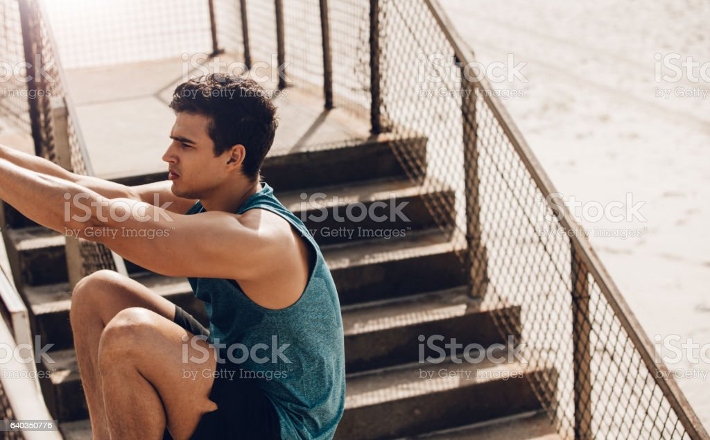 Fitness male stretching outdoors at the beach stock photo