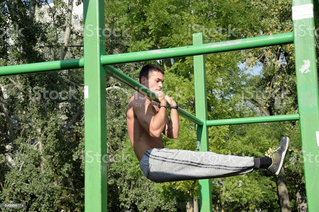 Fitness man at the bar. Exercising outdoors. Street workout. stock photo
