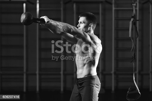 944655208 istock photo Fitness man doing a weight training by lifting kettlebell 626207416