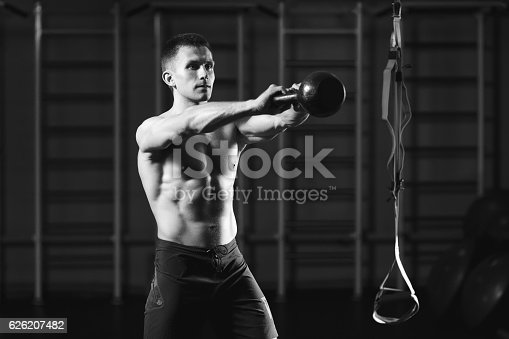 944655208 istock photo Fitness man doing a weight training by lifting kettlebell 626207482