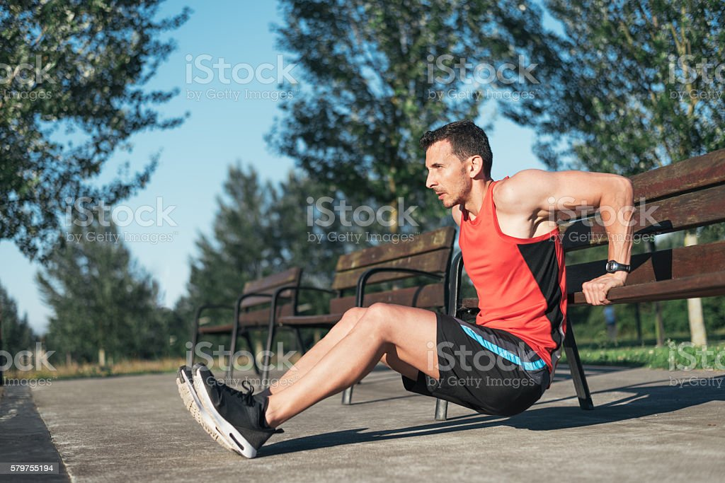 Fitness man doing bench triceps dips outdoors while working out - foto de stock
