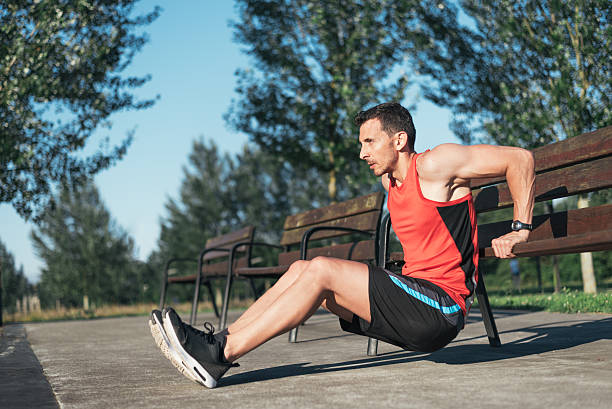 Fitness man doing bench triceps dips outdoors while working out stock photo