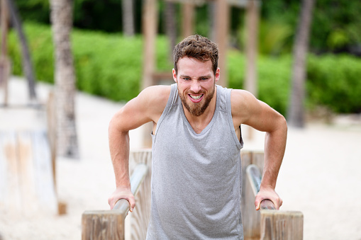 Fitness man doing dips at outdoor gym workout. Male athlete doing strength training on parallel bars in monkey jungle gym on beach. Guy exercising arms doing hard exercises.