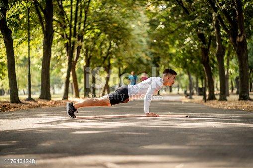 Fitness man doing push ups in park