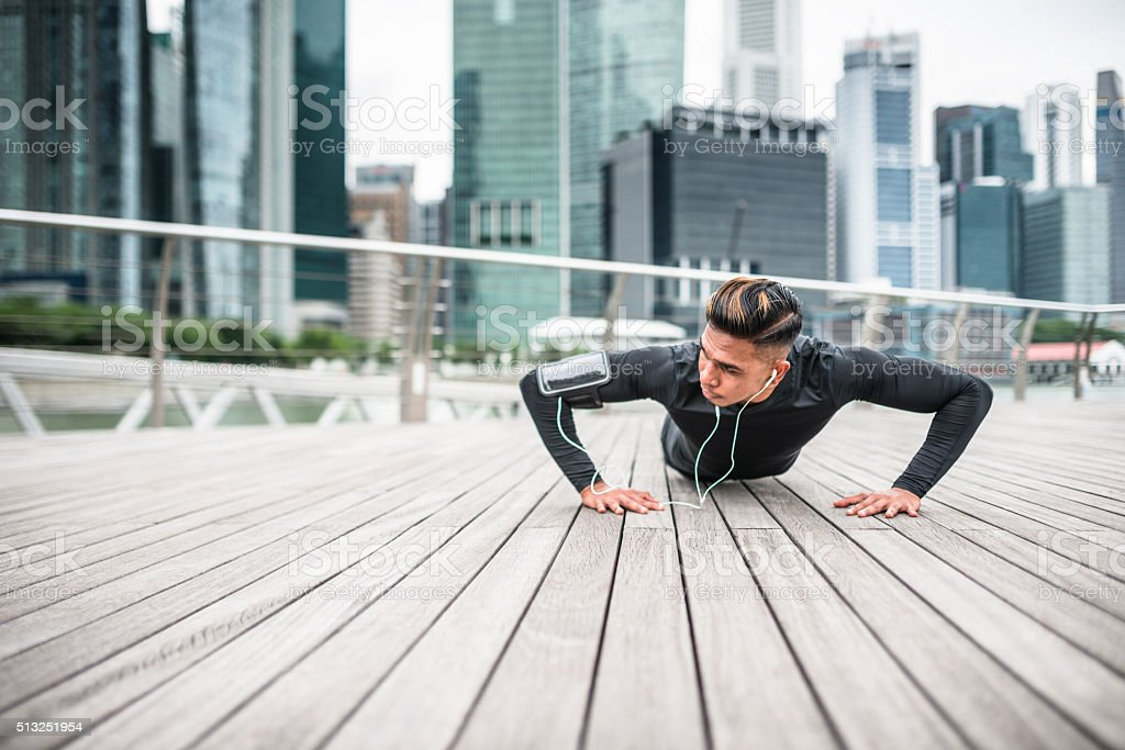 Fitness man doing push-ups in singapore city stock photo