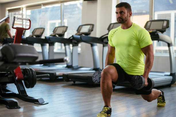 fitness man doing steps with weights - lunge stock photos and pictures