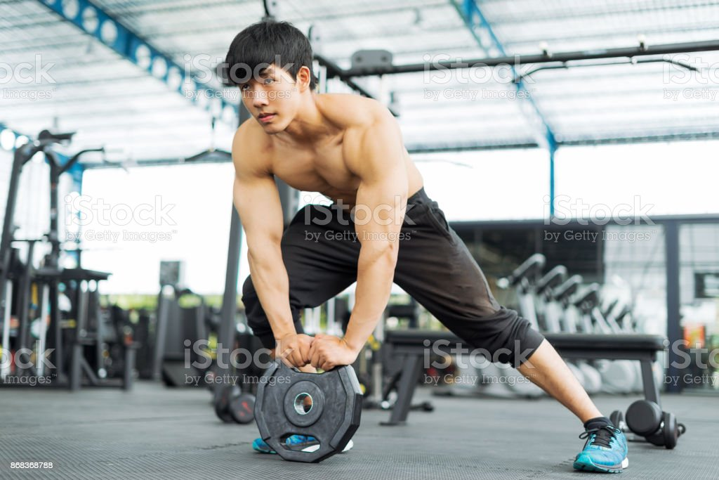 Fitness-Mann im training zeigt Übungen mit Hanteln im Fitnessstudio – Foto