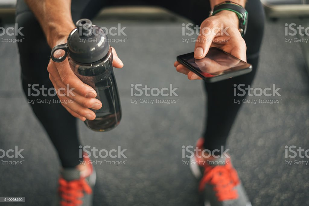 Fitness man looking to the phone for motivation before workout stock photo