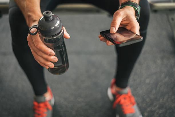 Homem de Ginástica, olhando para o telefone para motivação antes do exercício - foto de acervo