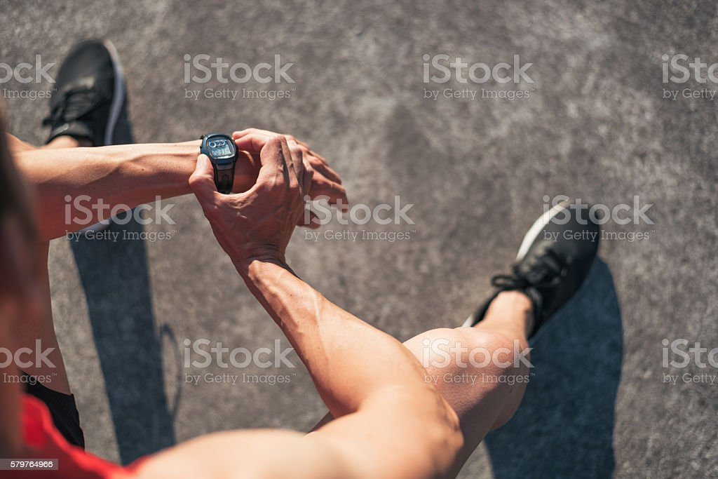 Fitness man resting during outdoor cross training reseting watch counter stock photo