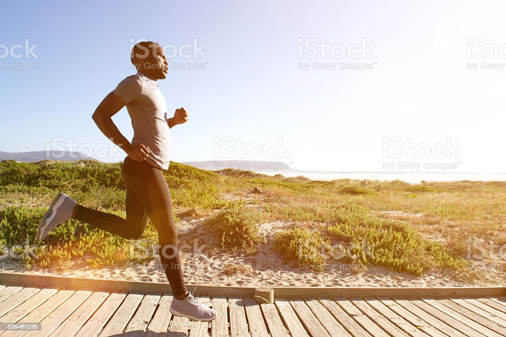 Fitness man running on the boardwalk at the beach stock photo