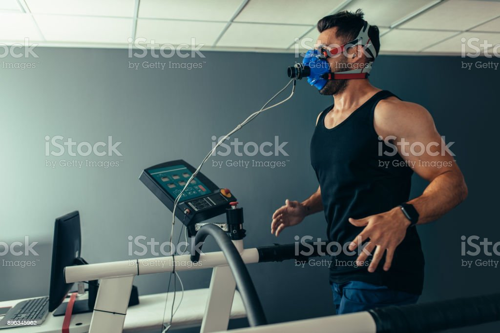 Fitness man running on treadmill testing his performance stock photo