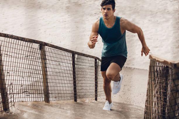 fitness man running up the steps on beach - treppe außen stock-fotos und bilder