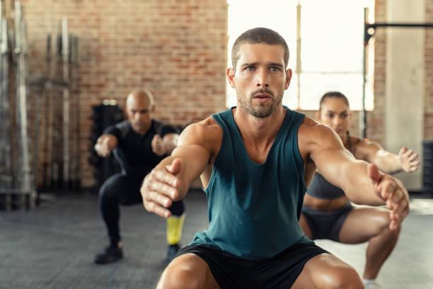 fitness man squatting with class at gym - training imagens e fotografias de stock