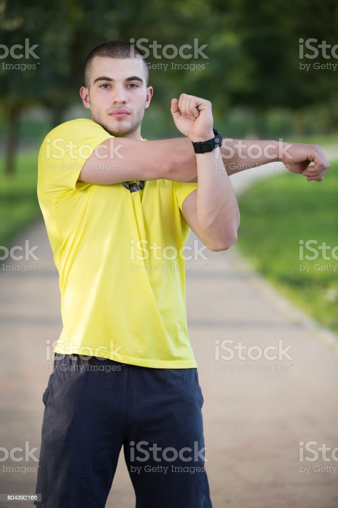 Fitness man stretching arm shoulder before outdoor workout. Sporty male athlete in an urban park warming up. stock photo
