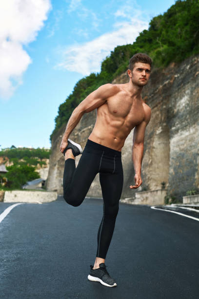 fitness man stretching body, exercising before running outdoor. sports workout - carpet runner stock photos and pictures