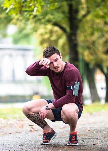 fitness mann dehnung der wadenmuskulatur nach dem lauf in berlin - laufende tattoos stock-fotos und bilder