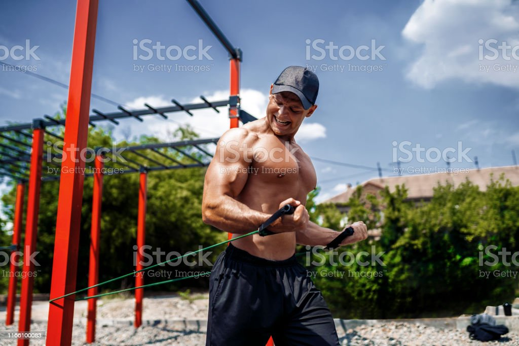 Fitness man training chest with resistance bands at street gym yard....