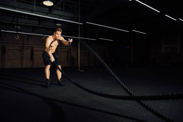 Fitness man workout with battle ropes at gym. training exercise fitted body in club. Torso stock photo