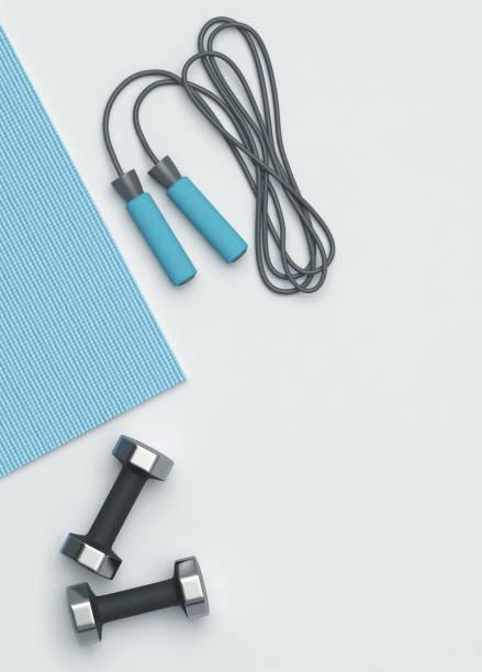 fitness mat, dumbbells and jumping rope on the floor - attrezzatura per esercizi foto e immagini stock