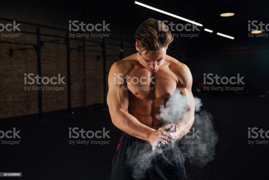 Fitness model trainer rubs his hands with chalk and talc so that fingers do not slip or slide stock photo
