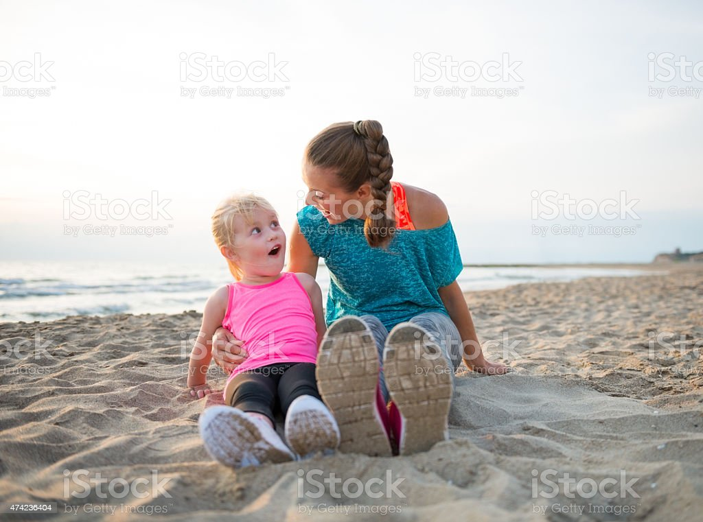 Fitness mother and surprised baby girl sitting on beach stock photo