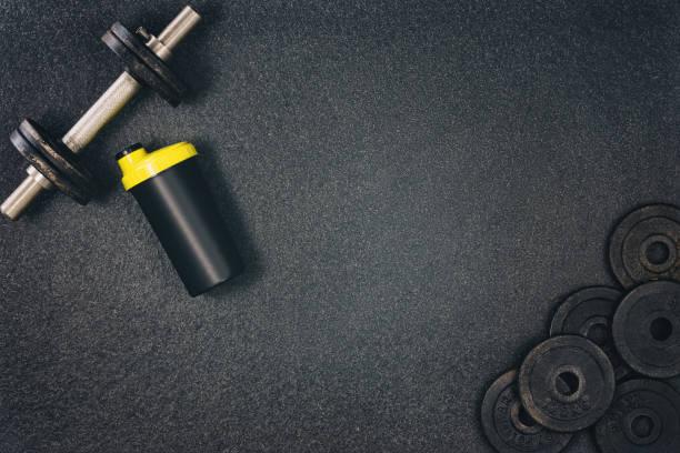 Fitness oder Bodybuilding-Hintergrund. Hanteln auf dem Boden des Fitnessstudios, oben mit Blick – Foto