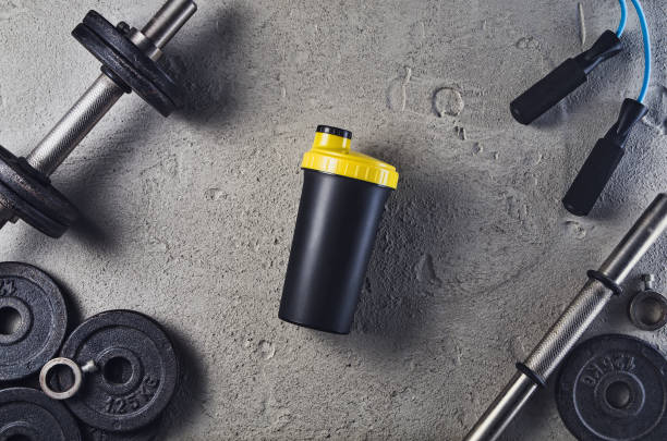 Fitness or bodybuilding background. Dumbbells on gym floor, top view Fitness or bodybuilding concept background. Product photograph of old iron dumbbells on grey, conrete floor in the gym. Photograph taken from above, top view with lots of copy space cocktail shaker stock pictures, royalty-free photos & images