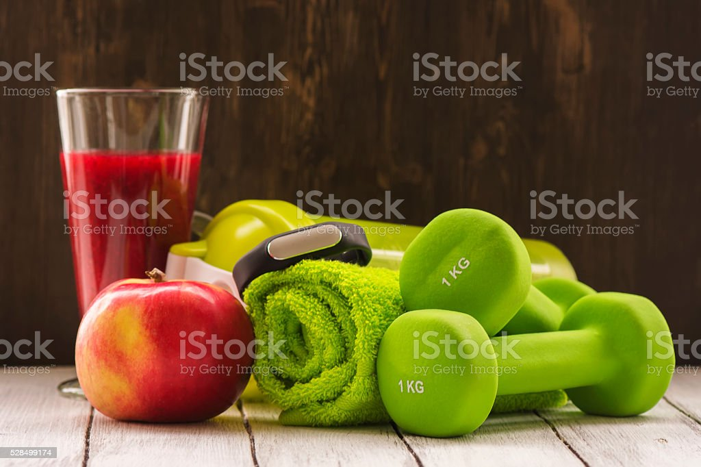 Fitness or diet concept: dumbbells, fresh red smoothie, apple stock photo